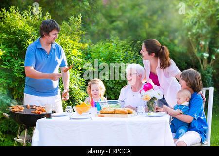 Grill Garten-Grillparty. Glückliche Großfamilie Grill-Lunch mit Großmutter Verzehr von Fleisch mit Salat im Garten - Stockfoto