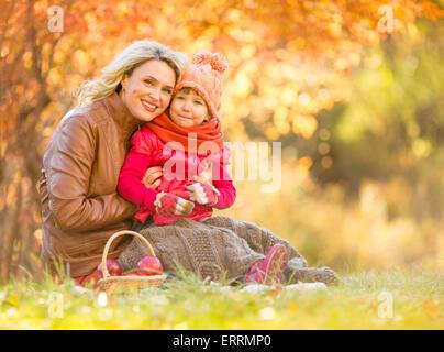 Glückliche Mutter und Kind sitzt im Freien im Herbst - Stockfoto