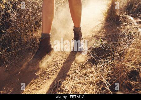 Junge Frau die Füße als She-Wanderungen auf einem Bergweg mit Staubwolke. Frau auf Feldweg in Landschaft wandern. - Stockfoto