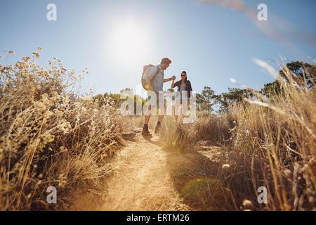 Im Freien Schuss des jungen Paares auf Wanderung zu Fuß auf Schmutz trail in Bergen, die Hand in Hand. Junger Mann - Stockfoto