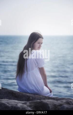 ein Mädchen in einem weißen Kleid sitzt auf den Felsen am Meer - Stockfoto