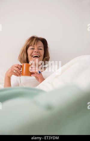 Ältere Frau in ihrem Schlafzimmer, trinken Tee am Morgen, München, Bayern, Deutschland - Stockfoto