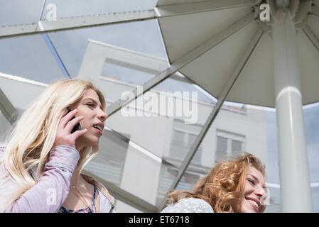 Teenager-Mädchen mit ihrer Freundin telefonieren mit Handy, München, Bayern, Deutschland - Stockfoto