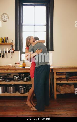 Glückliche junge Frau wird von ihrem Freund in der Küche umarmte. Fröhliches junges Paar umarmen einander Morgen - Stockfoto