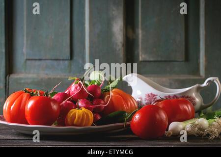 Haufen von Frischgemüse reif bunte Tomaten, Chilischoten, Frühlingszwiebeln und Bündel Radieschen auf Vintage Platte - Stockfoto