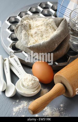Zutaten und Werkzeuge, um russischen Pelmeni auf grauem Hintergrund - Stockfoto