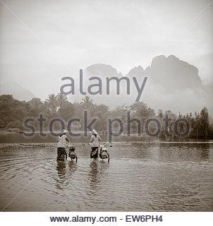 Zwei Frauen mit konischen asiatischen hüten schieben Fahrräder durch einen seichten Fluss in Vang Vien, Laos. - Stockfoto