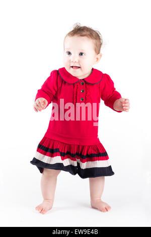 Süße Babymädchen in einem roten Kleid machen ihre ersten Schritte - Stockfoto