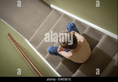 Ein Kind sitzt auf der Treppe mit dem Kopf in seine Hände suchen verärgert - Stockfoto