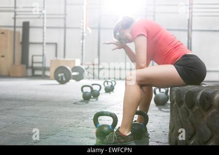 Erschöpfte Frau sitzt auf Reifen in Crossfit gym - Stockfoto