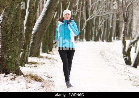 Junge Sportlerin im Winter Park Joggen. Sportlerin auf verschneiten Weg laufen - Stockfoto