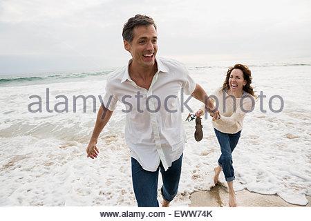 Verspieltes paar spielen im Meer Surfen - Stockfoto