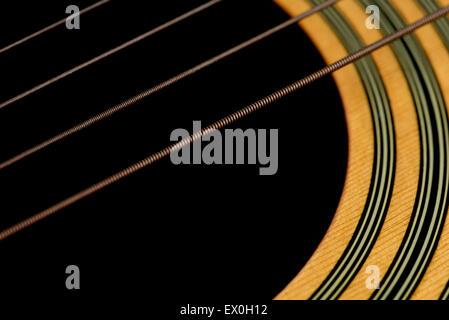 Eine abgewinkelte Makroaufnahme der akustischen Gitarrensaiten und das Holz rund um das Schalloch der Gitarre. - Stockfoto