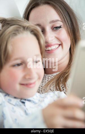 Junge und Teenager-Mädchen mit Digital-Tablette lächelnd - Stockfoto