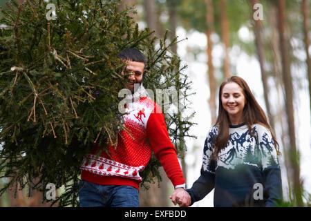 Junges Paar Tragetasche Weihnachtsbaum auf Schultern in Wäldern - Stockfoto
