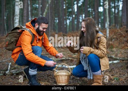 Junge Wandern paar Tannenzapfen im Wald sammeln - Stockfoto