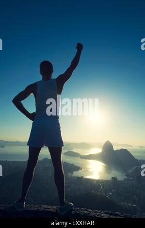 Inspirierende Silhouette der Athlet in der weißen Sport einheitliche Stellung mit Champion Arm angehoben Skyline - Stockfoto