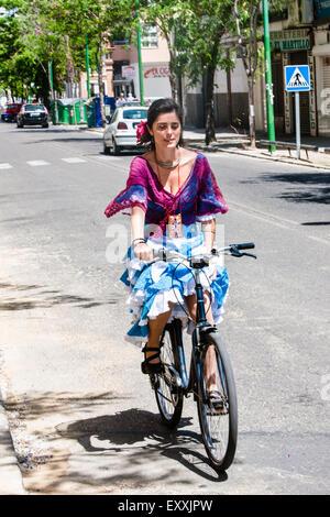 Junge Frau mit dem Fahrrad in Tracht Sevilla in Sevilla, Sevilla, Andalusien, Spanien, Europa-Center. Während der - Stockfoto