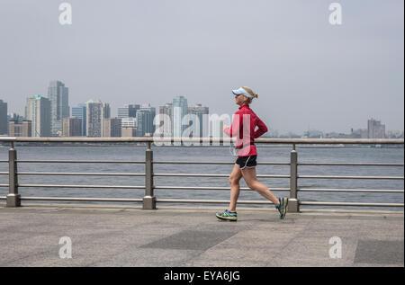 Frau, laufen, Joggen im Hudson River Park.  Manhattan, Jersey City im Hintergrund. NEW YORK CITY. USA. - Stockfoto