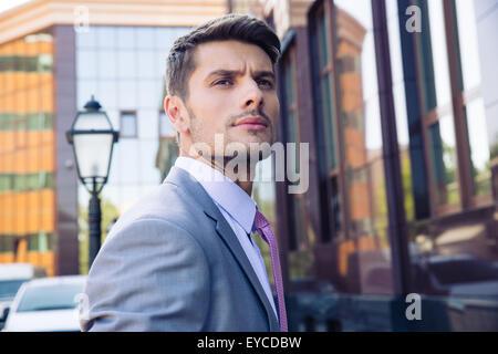 Porträt eines nachdenklich Geschäftsmann stand im Freien in der Nähe Bürogebäude und wegsehen - Stockfoto