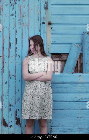eine Mädchen in einem geblümten Kleid steht vor einer blauen Wand aus Holz - Stockfoto
