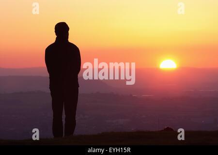 Silhouette der Mann stand auf Glastonbury Tor bei Sonnenuntergang; Glastonbury, Somerset, England, Uk - Stockfoto