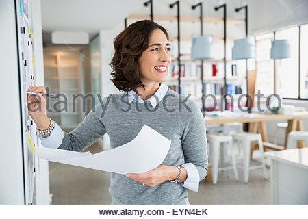 Lächelnd Architekt mit Blaupausen am Whiteboard im Büro - Stockfoto