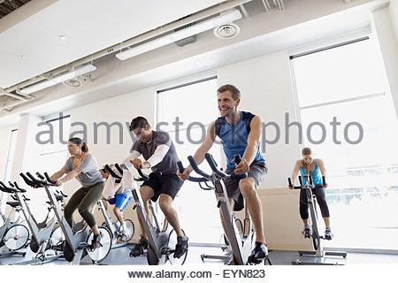 Spin-Klasse auf stationären Fahrrädern in Turnhalle - Stockfoto