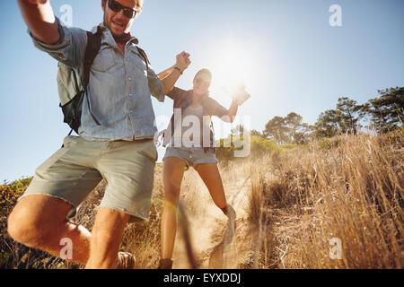 Porträt der glückliche junge Paare, die Spaß auf ihrer Wanderung, den Bergpfad hinab gleiten. Kaukasische Wanderer - Stockfoto