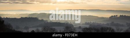 Niedrige Morgensonne im Winter steigt über die nebligen Landschaft aus Newlands Corner, Guildford, Surrey - Stockfoto