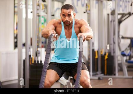Junger Mann bereitet sich mit Kampf Seilen in einem Fitnessstudio trainieren - Stockfoto