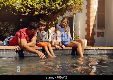 Porträt der jungen Familie mit zwei Kindern, die von ihrem Pool Spaß entspannend. Eltern mit Kinder sitzen auf dem - Stockfoto