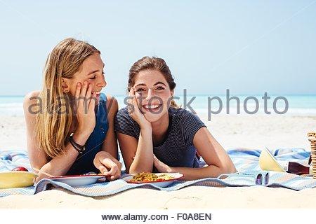 Porträt von zwei jungen Freundinnen auf der Picknickdecke am Strand liegend - Stockfoto
