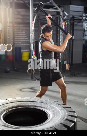 Junger Mann Hämmern große Reifen in Turnhalle - Stockfoto