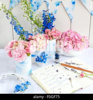 Sommer-Blumen-Vorbereitungen mit Zeitschrift, Feder und Tinte - Stockfoto