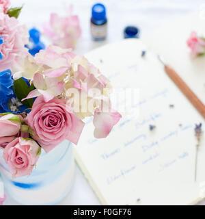 Nahaufnahme des Sommer-Blumen-Arrangement mit Zeitschrift, Feder und Tinte im Hintergrund - Stockfoto