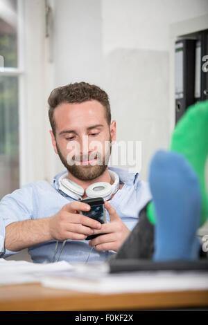 Junger Mann im Büro mit Füßen auf Schreibtisch Blick auf Handy - Stockfoto