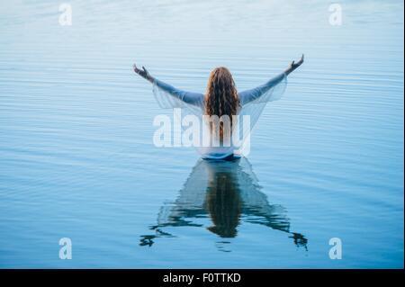 Rückansicht des jungen Frau im blauen See mit offenen Armen - Stockfoto