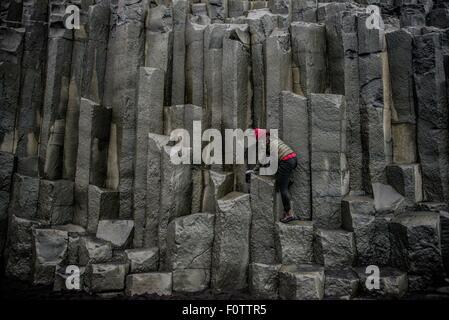Weibliche Touristen Klettern auf Felsformation, Reynisfjara, Island - Stockfoto