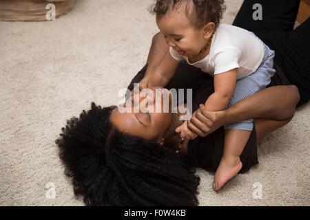 Mitte Erwachsene Frau spielt mit Kleinkind Tochter auf Teppich - Stockfoto