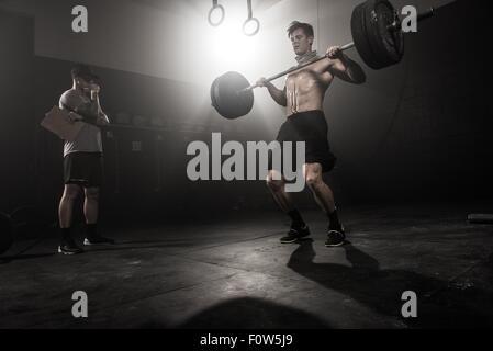 Mitte erwachsenen Mannes Langhantel, heben, während Trainer auf niedrigen Winkel Ansicht sieht - Stockfoto