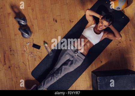 Draufsicht des Lächelns weibliche trainieren Sie im Fitness-Studio. Muskulöse junge Frau liegt auf Gymnastikmatte - Stockfoto