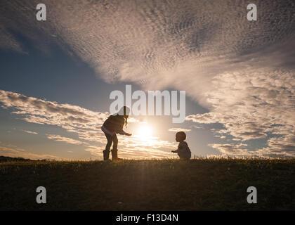 Silhouette eines Mädchens mit einem Baby laufen lernen - Stockfoto