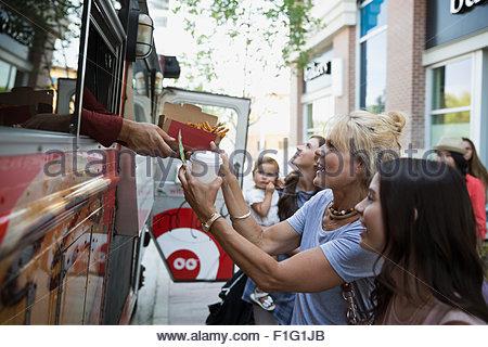 Kunden, die Lebensmittel außerhalb Imbisswagen - Stockfoto