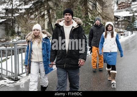 Vier Freunde tragen Winterkleidung zu Fuß - Stockfoto