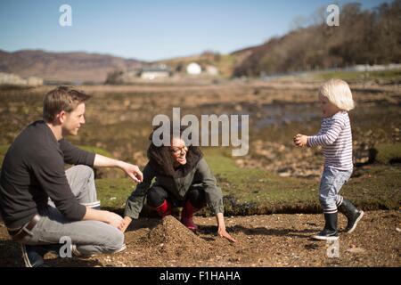 Mutter und Vater mit Sohn, machen Haufen Erde spielen - Stockfoto