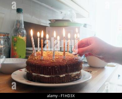 Hand der jungen Frau platzieren Kerzen auf der Geburtstagstorte - Stockfoto