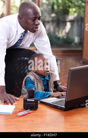 Ein afrikanischer Junge sitzt an seines Vaters Schreibtisch, auf ein Leptop zu spielen, während sein Vater über - Stockfoto