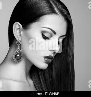 Porträt von schöne Brünette Frau mit Ohrring. Perfektes Make-up. Modefoto. Schwarz / weiß - Stockfoto
