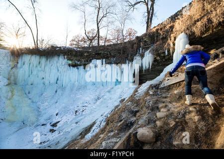 Eine Frau im Mantel, Handschuhe und Stiefel Wanderungen auf rutschigen Felsen zu gefrorenen Minnehaha Fälle im Winter, - Stockfoto